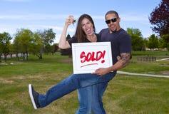 Coppie interrazziali felici con il segno venduto Fotografia Stock Libera da Diritti