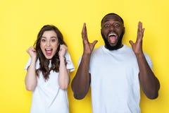 Coppie interrazziali felici di grido in magliette bianche che posano per la macchina fotografica in studio fotografia stock libera da diritti