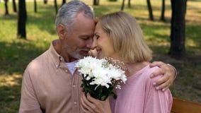 Coppie invecchiate amorose che frugano durante la data romantica in parco, presente del mazzo dei fiori fotografie stock libere da diritti