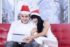 Coppie ispane in cappello di Santa facendo uso della compressa Fotografia Stock