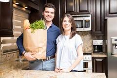 Coppie ispane con il sacchetto della spesa della drogheria in cucina fotografie stock