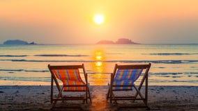 Coppie le chaise-lounge della spiaggia sulla spiaggia abbandonata al tramonto distendasi Fotografia Stock