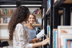 Coppie le giovani belle ragazze in vestiti alla moda casuali che stanno gli scaffali per libri vicini in biblioteca, esaminantese Fotografie Stock