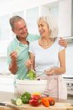 Coppie maggiori che preparano insalata in cucina Immagini Stock