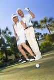 Coppie maggiori felici che giocano golf che mette sul verde immagini stock libere da diritti