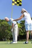 Coppie maggiori felici che giocano insieme golf fotografie stock