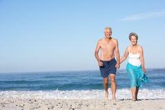 Coppie maggiori in vacanza che funziona lungo la spiaggia immagine stock libera da diritti
