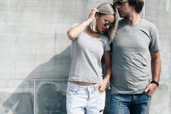 Coppie in maglietta grigia sopra la parete della via Immagine Stock