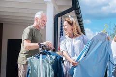 Coppie mature amorose che esaminano i vestiti mentre visitando vendita di oggetti usati di fine settimana immagine stock