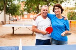 Coppie mature che abbracciano vicino al ping-pong fotografia stock libera da diritti