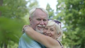 Coppie mature che baciano e che guardano nel sorridere della macchina fotografica Donna senior che abbraccia il suo marito Riposo video d archivio