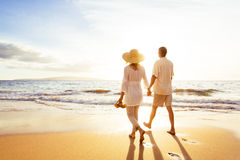 Coppie mature che camminano sulla spiaggia al tramonto fotografia stock