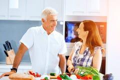 Coppie mature che cucinano a casa immagini stock