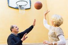 Coppie mature che giocano pallacanestro in patio Fotografie Stock Libere da Diritti