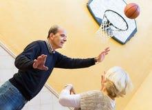 Coppie mature che giocano pallacanestro in patio Immagini Stock