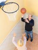 Coppie mature che giocano pallacanestro in patio Immagini Stock Libere da Diritti