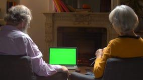 Coppie mature che guardano per greenscreen il computer portatile del modello video d archivio