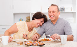 Coppie mature che mangiano pranzo a casa immagini stock libere da diritti