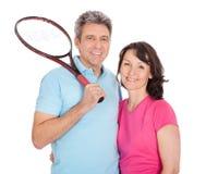 Coppie mature con le racchette di tennis Immagine Stock