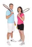 Coppie mature con le racchette di tennis Fotografie Stock