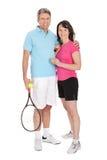 Coppie mature con le racchette di tennis Immagini Stock