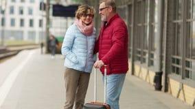 Coppie mature con una valigia sul binario del treno che ride e che abbraccia Pensionati di viaggio Un uomo e una donna stanno dur archivi video