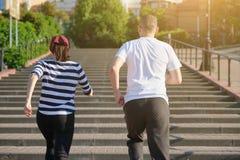 Coppie mature correnti all'aperto Uomo e una donna di 40 anni che corrono di sopra, vista dalla parte posteriore immagini stock libere da diritti
