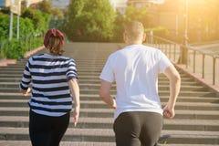 Coppie mature correnti all'aperto Uomo e una donna di 40 anni che corrono di sopra, vista dalla parte posteriore fotografia stock libera da diritti