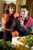 Coppie mature in cucina con la verdura fresca fotografia stock