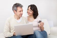 Coppie mature facendo uso del computer portatile a casa Immagine Stock