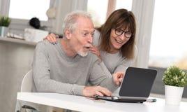 Coppie mature felici che hanno una buona sorpresa sul computer portatile fotografia stock libera da diritti