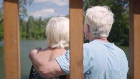 Coppie mature felici che si siedono sul banco vicino al fiume, pieno d'ammirazione natura Donna senior che bacia il suo marito sv video d archivio