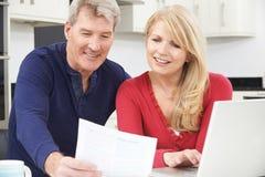 Coppie mature sorridenti che esaminano le finanze domestiche Fotografia Stock