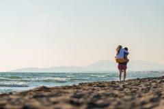Coppie Medio Evo romantico felice che godono di bella passeggiata di tramonto sulla spiaggia immagine stock