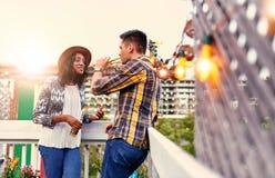 coppie millenial Multi-etniche che flirtano mentre bevendo sul terrasse del tetto al tramonto Fotografia Stock Libera da Diritti