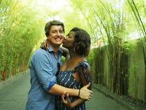 Coppie miste attraenti e felici di etnia che stringono a sé all'aperto con l'amica o la moglie afroamericana nera attraente e bel fotografie stock libere da diritti