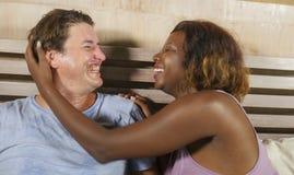 Coppie miste di etnia nell'amore che stringe a s? insieme a casa a letto con la bella donna afroamericana nera allegra ed il bian fotografia stock
