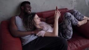 Coppie multietniche amorose che si trovano sullo strato e sulla conversazione rossi L'uomo e la donna in pigiami si tengono per m archivi video