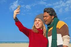 Coppie multietniche che prendono selfie facendo uso dello smartphone Immagine Stock Libera da Diritti