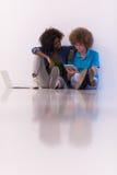 Coppie multietniche che si siedono sul pavimento con un computer portatile e una compressa Fotografia Stock