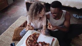 Coppie multietniche felici che si siedono sul flusso, abbraccianti e mangianti alimenti a rapida preparazione Alimentazione della Immagini Stock