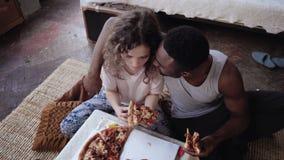 Coppie multietniche felici che si siedono sul flusso, abbraccianti e mangianti alimenti a rapida preparazione Alimentazione della Immagini Stock Libere da Diritti
