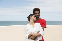 Coppie multietniche sulla spiaggia fotografie stock