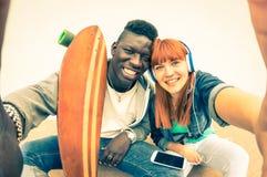 Coppie multirazziali di amore dei pantaloni a vita bassa che prendono il selfie urbano di modo immagini stock libere da diritti