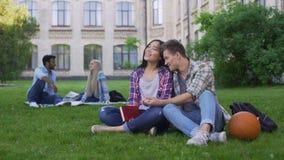 Coppie multirazziali romantiche che si siedono sul prato inglese vicino all'accademia e che si godono di video d archivio