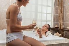 Coppie nel champagne bevente della vasca Fotografie Stock Libere da Diritti