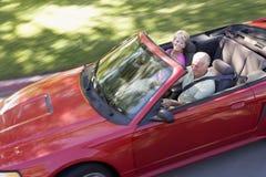 Coppie nel sorridere convertibile dell'automobile Immagini Stock