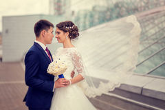Coppie nell'abbraccio della sposa e dello sposo di amore su un fondo di architettura urbana Il velo della sposa che fluttua nel v Fotografia Stock