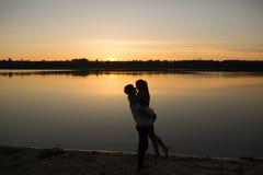 Coppie nell'alba sulla spiaggia fotografia stock