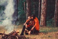 Coppie nell'amore al picnic con fuoco in foresta, alberi fotografie stock